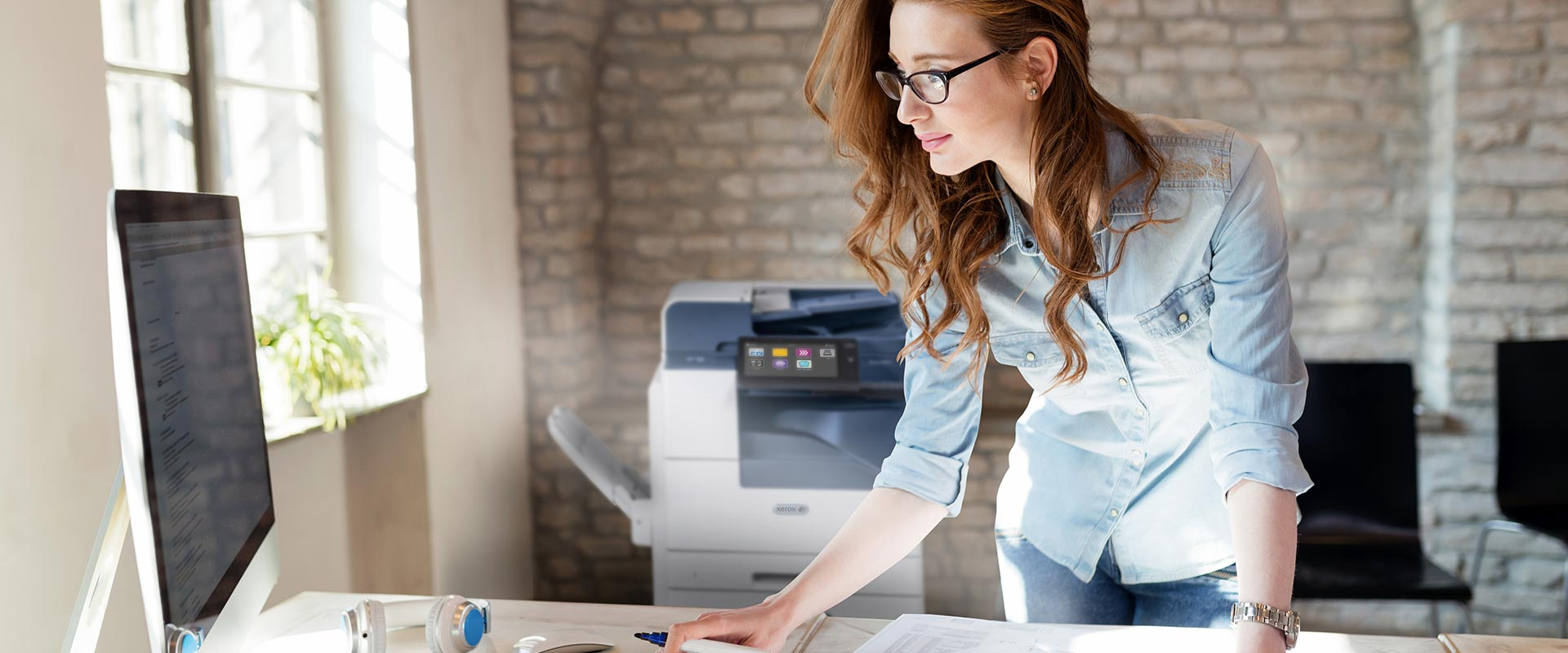 A young woman sending a print job from her computer to the office printer.