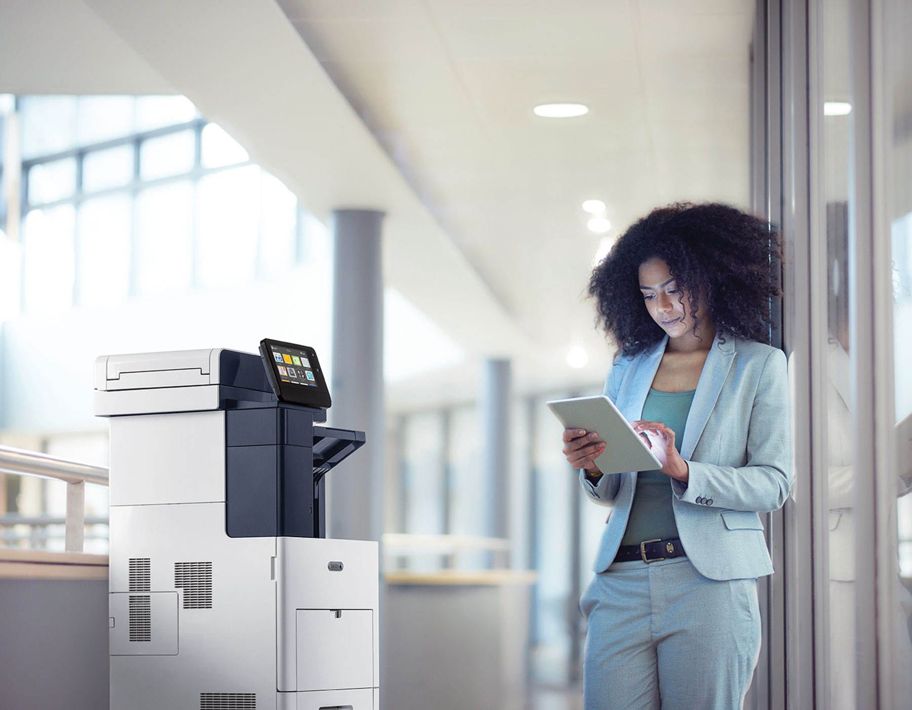 A young woman standing next to a large office printer while looking at her tablet.